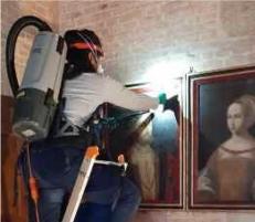 Fleur Foucher en train de dépoussiérer les peintures du château